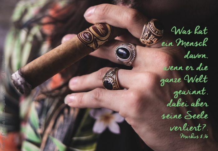 Mann mit beringter Hand und dicker Zigarre