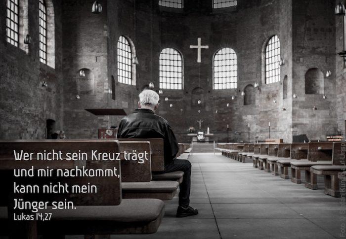 Mann sitzt in einer Kirche