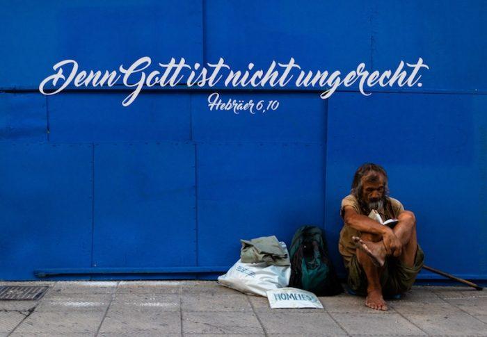 Obdachloser vor blauer Wand