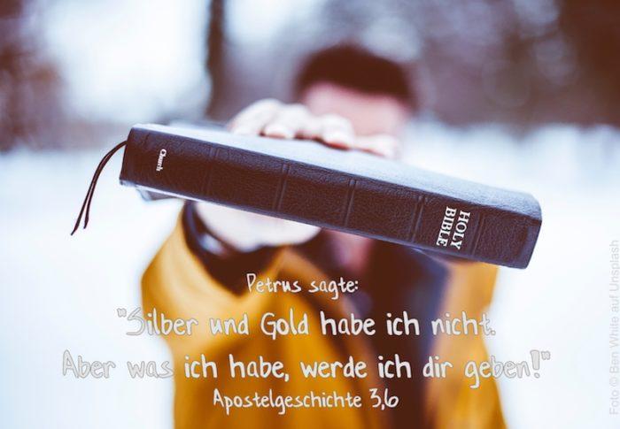 Mann hält Bibel in die Kamera