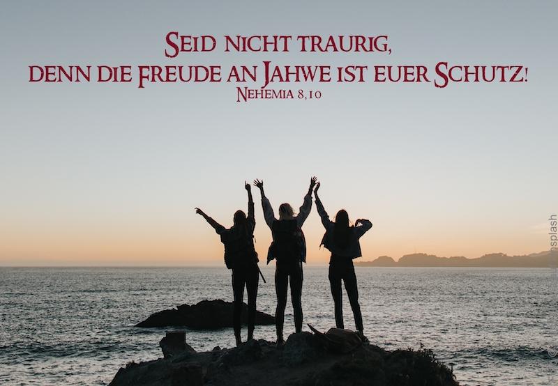 3 Personen strecken die Arme in den Himmel auf einem Felsen vor dem Meer