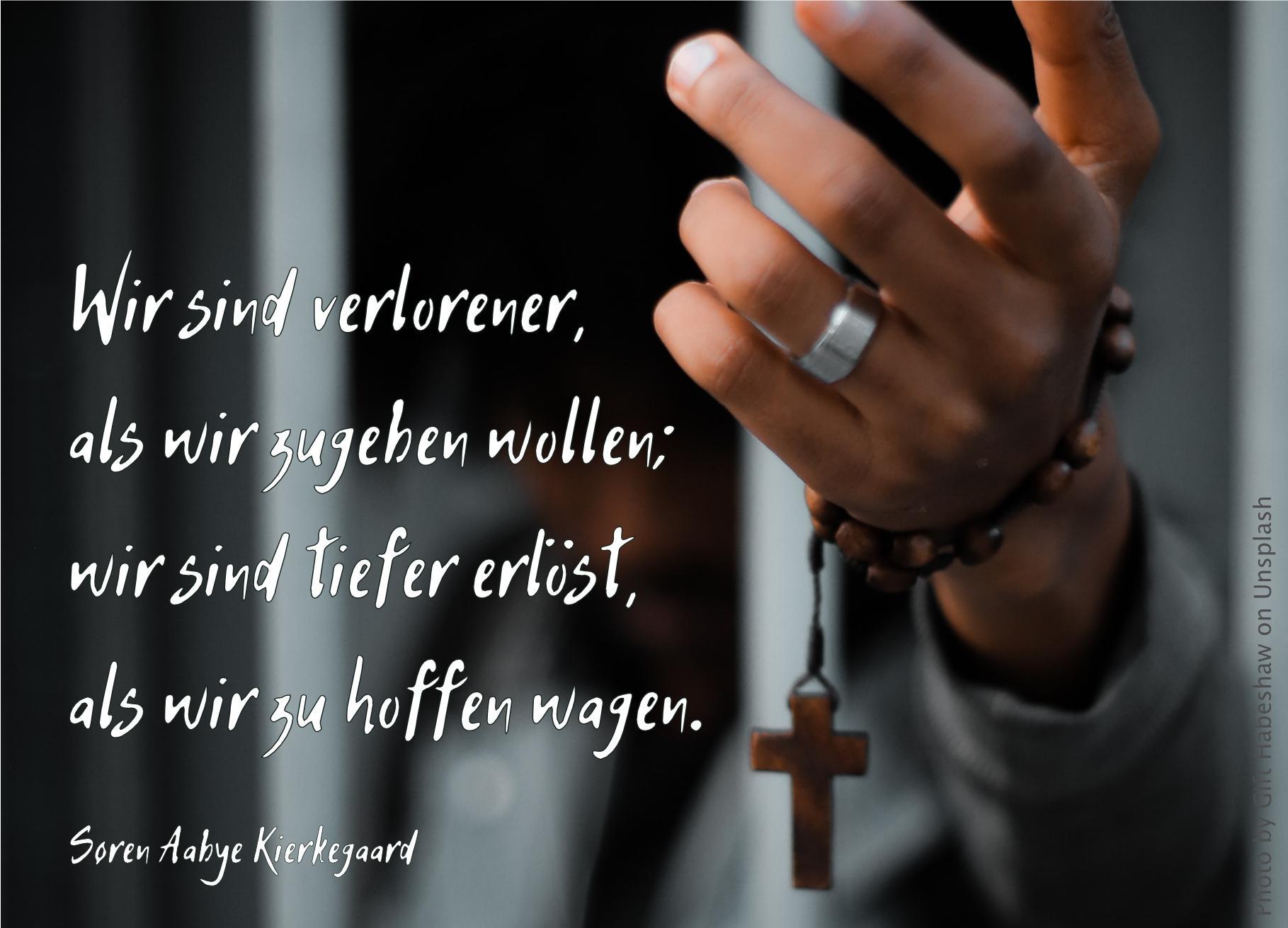 Hand zwischen Gittern mit Kreuz