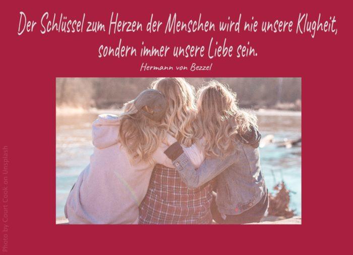 3 Frauen die Arm in Arm am See sitzen