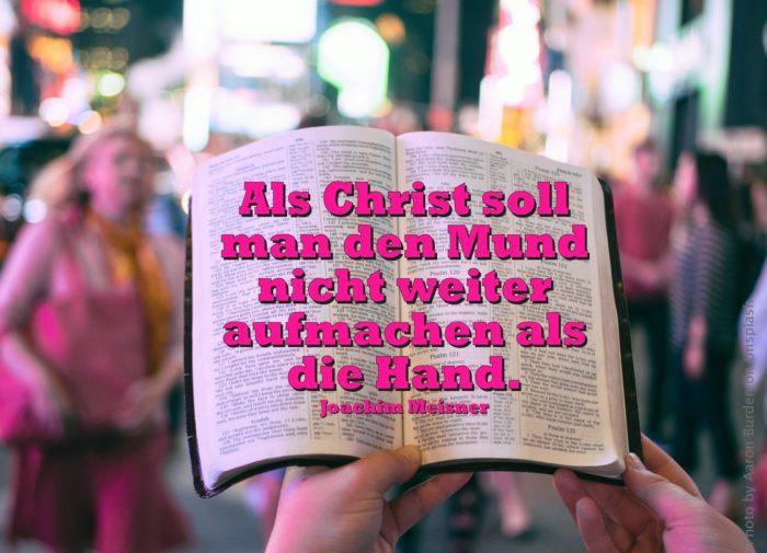 Aufgeschlagene Bibel in der Hand im Hintergrund verschwommene Menschen