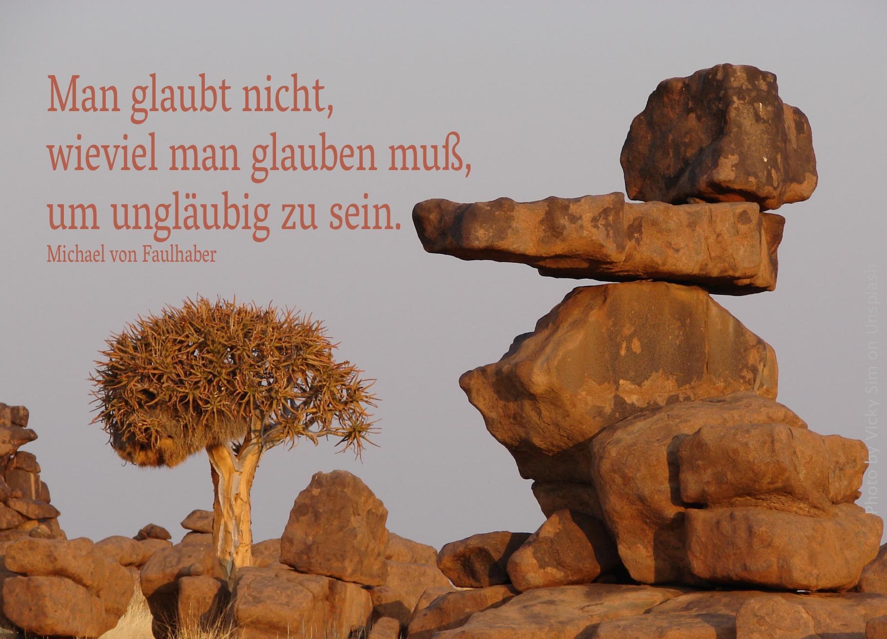 Aufeinander liegende Felsen in der Steppe mit Dornenbaum