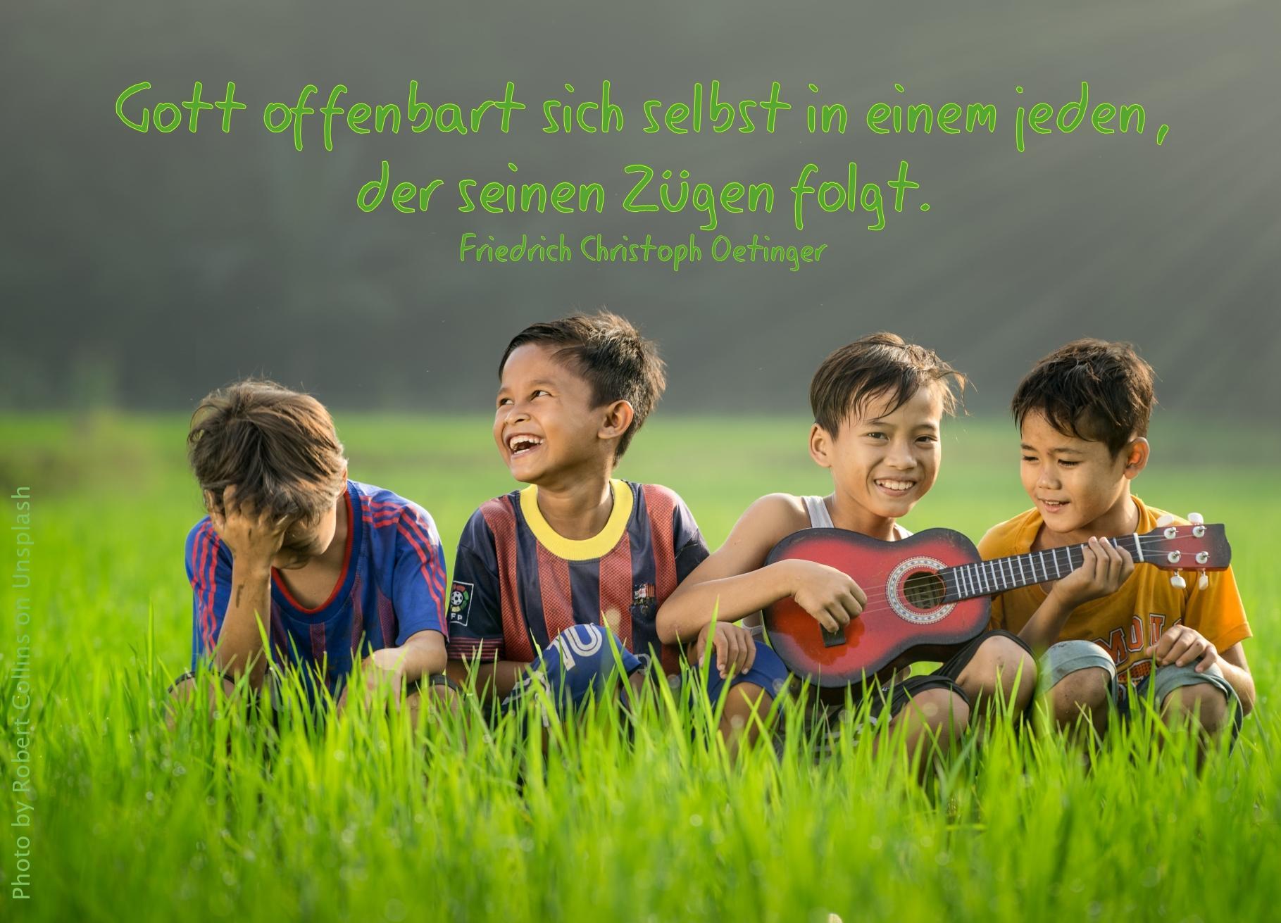 4 lachende Kinder im Gras mit kleiner Gitarre