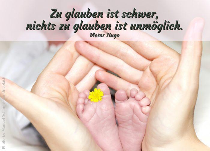 Hände, die Babyfüße halten