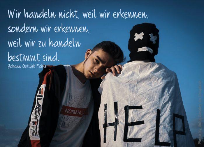 zwei junge Männer, einer mit einem weißen Umhang mit Aufschrift HELP