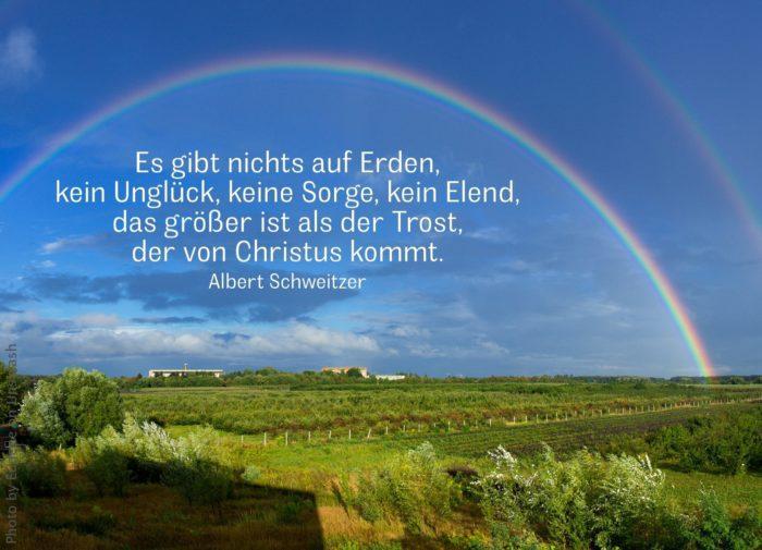 Großer Regenbogen spannt sich weit über grünem Land