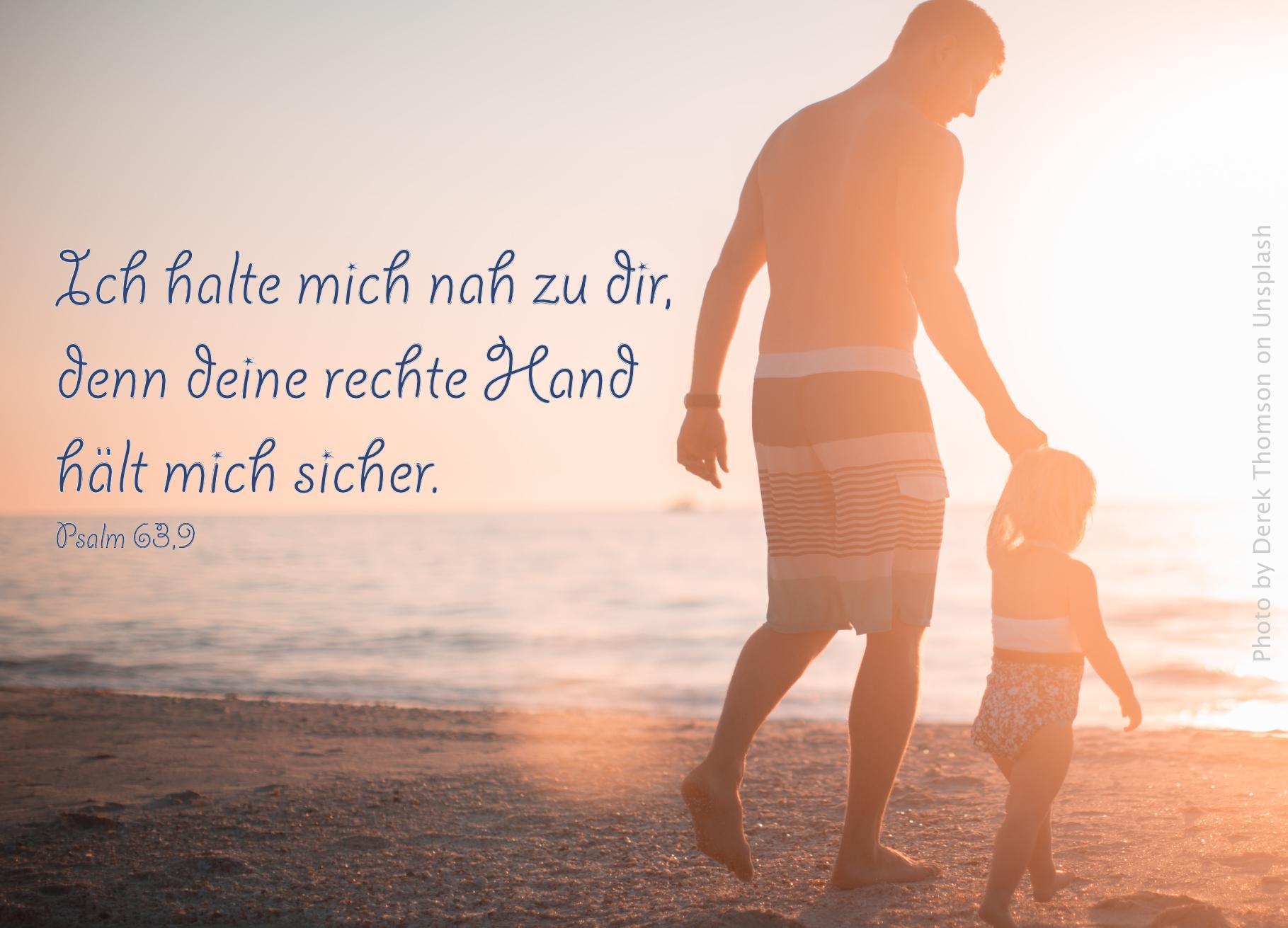 Mann mit Kind an der Hand am Strand