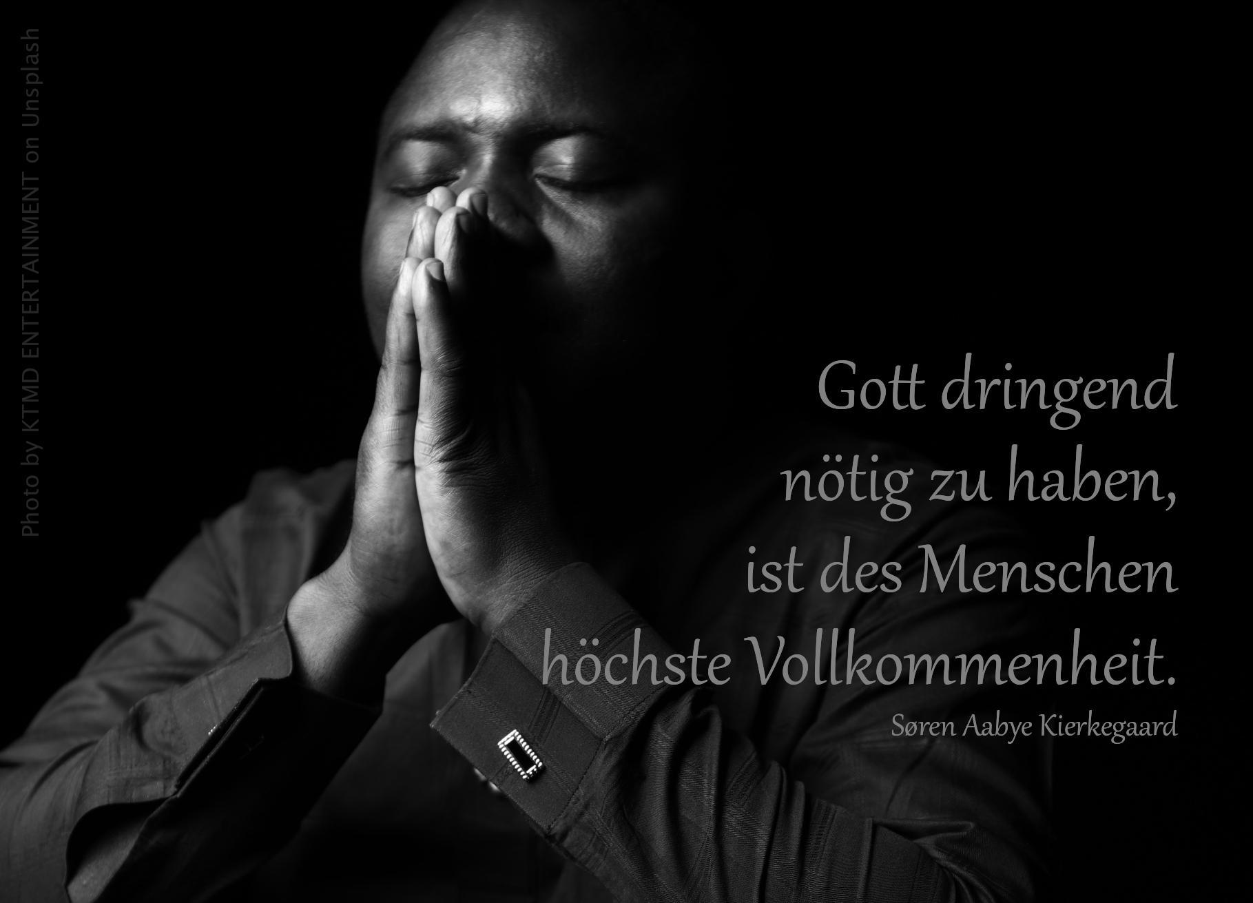 Mann hält betend die Hände vorm Gesicht
