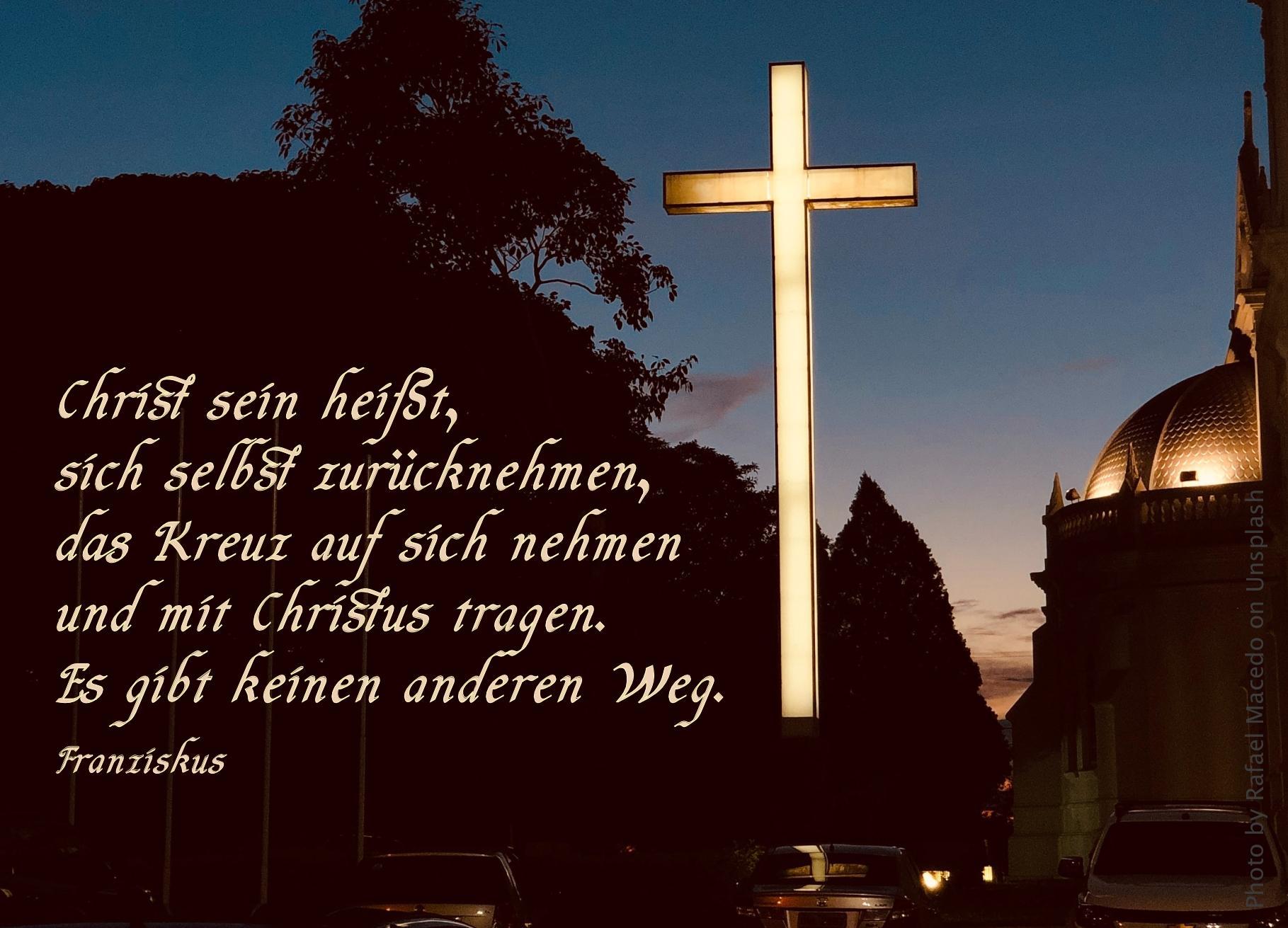 Von innen erleuchtetes Kreuz in dunkler Stadtshilouette