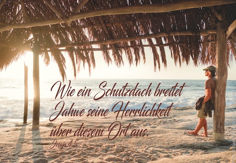 Mann lehnt am Strand an einer überdachten Palmhütte