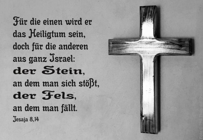 dunkles Kreuz mit Maserung auf grauer Wand