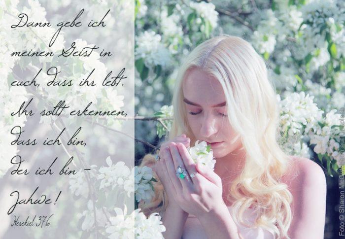 Frau riecht an weißen Blüten