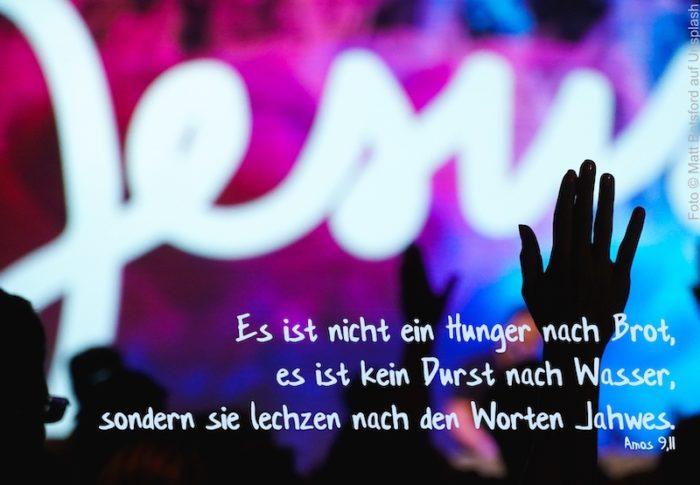 erhobene Hände vor bunter Wand mit Schriftzug Jesus