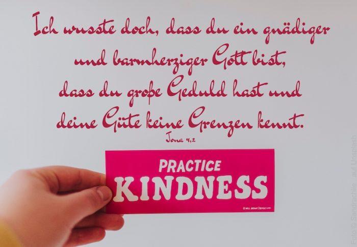 Hand hält Schild: Practice Kindness