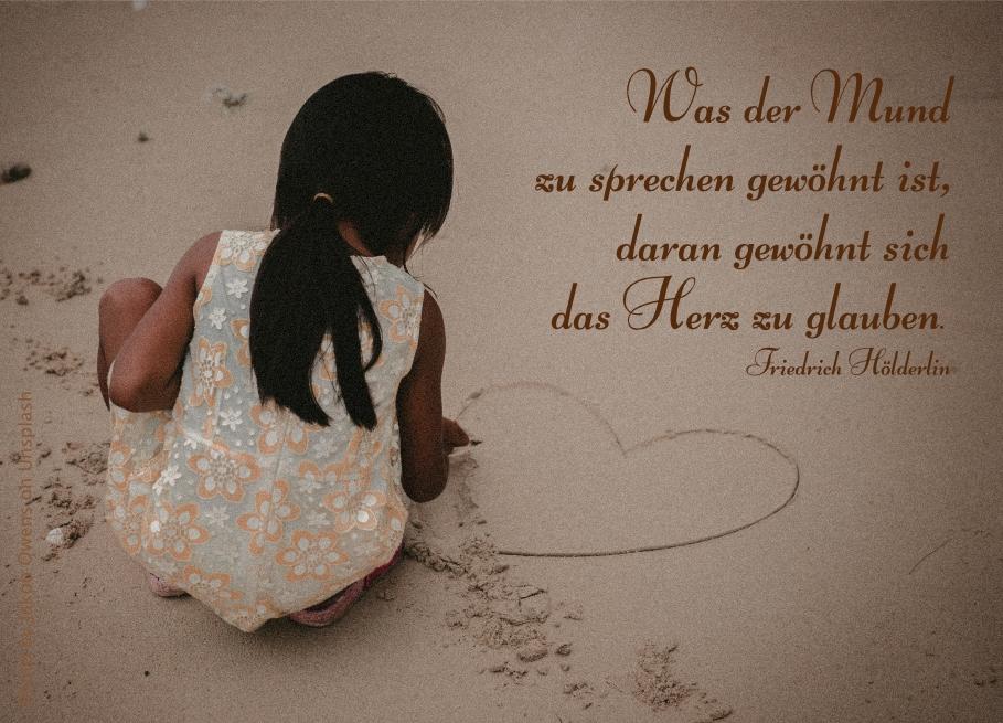 Mädchen zeichnet Herz in den Sand