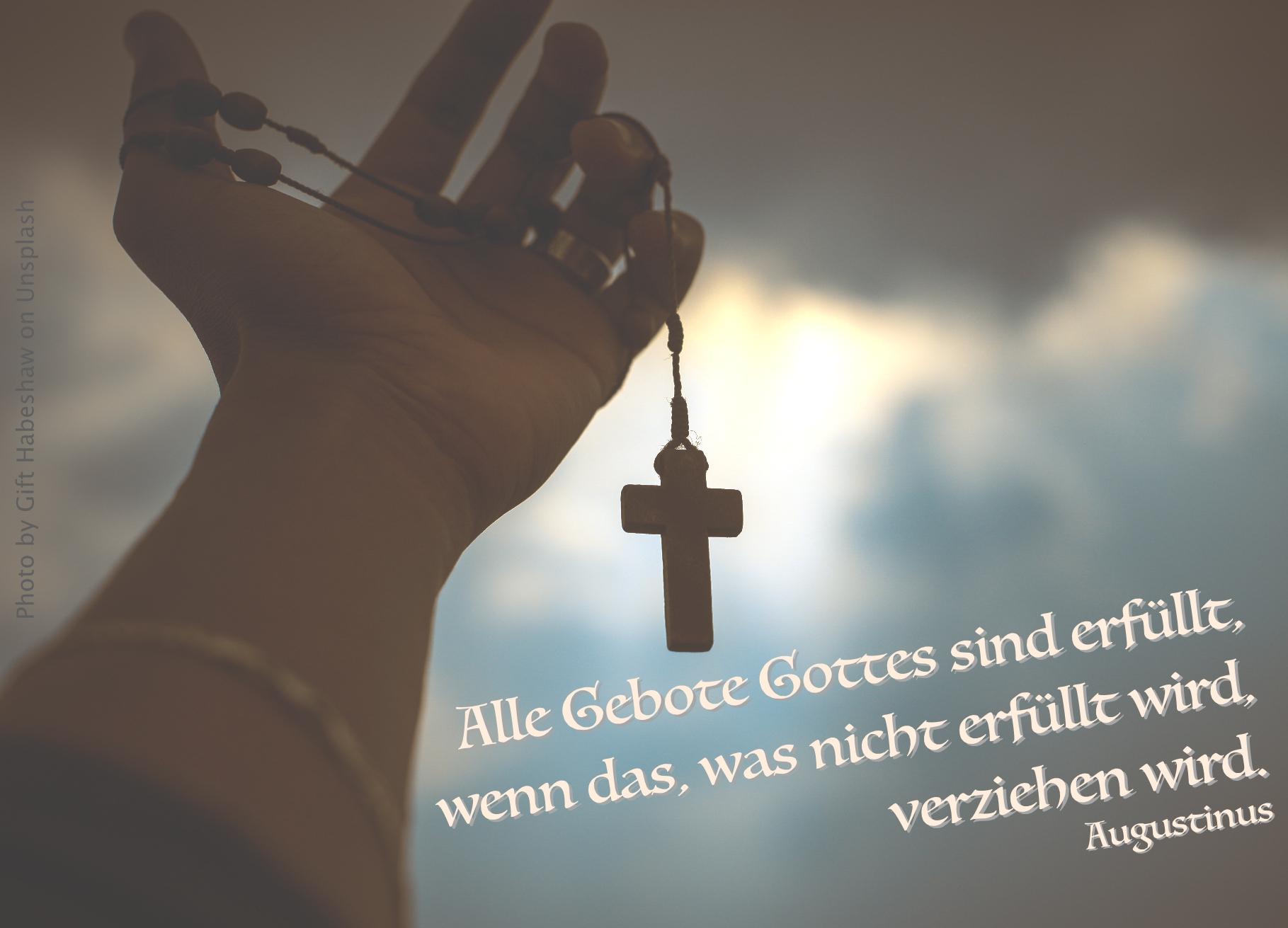 Hand mit Kreuzanhänger