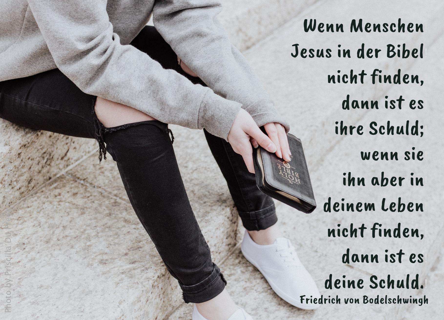 Person sitzt auf Treppe mit Bibel in der Hand