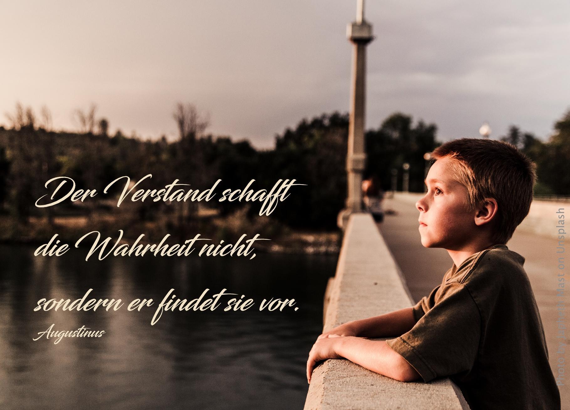 Junge steht auf Brücke und schaut in die Ferne