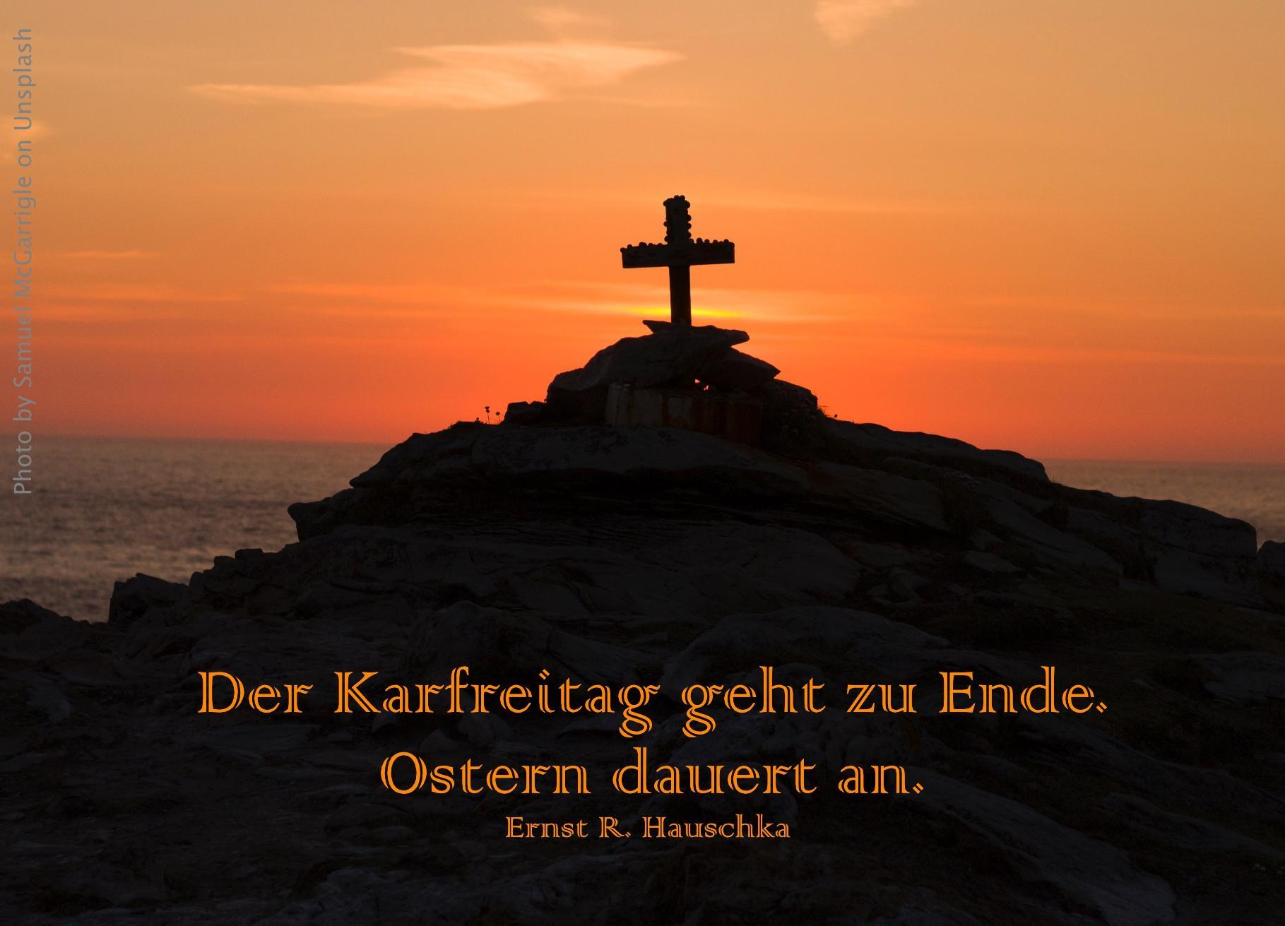 Kreuz auf Berg vor rotem Himmel