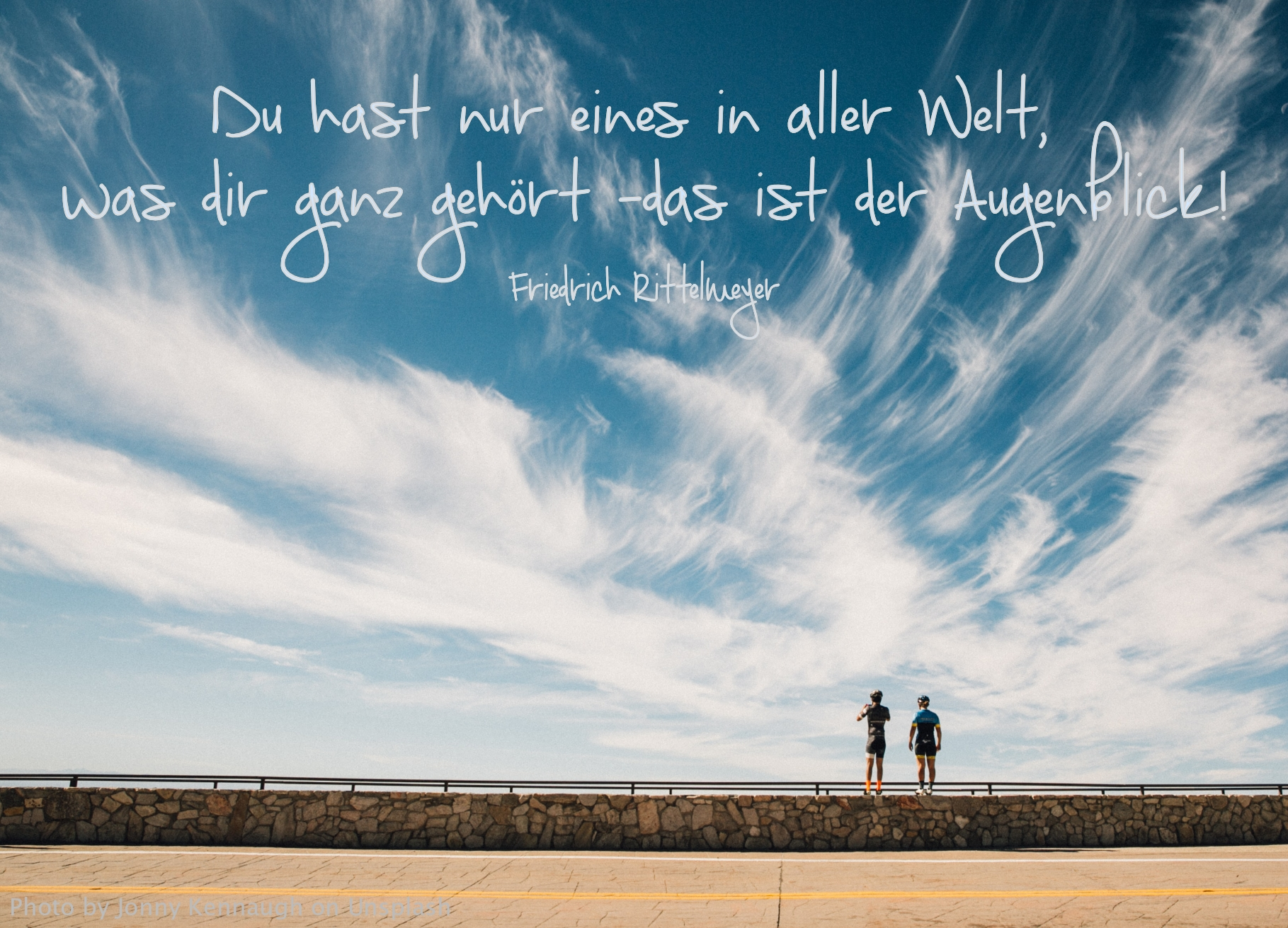 zwei Personen auf Steinmauer unter blauem wolkigen Himmel