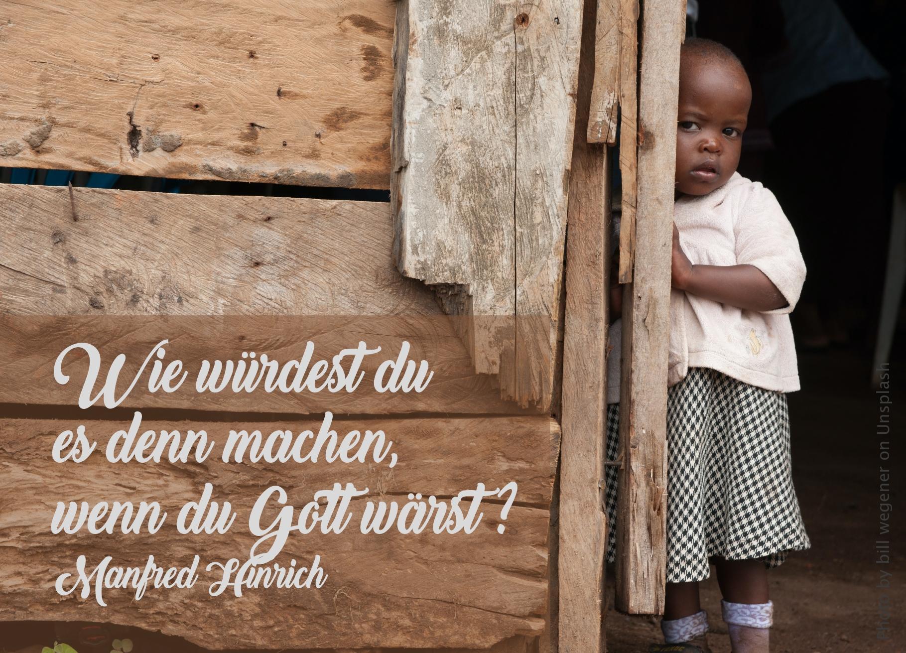 Kleines Mädchen steht im Türeingang einer einfachen Holzhütte