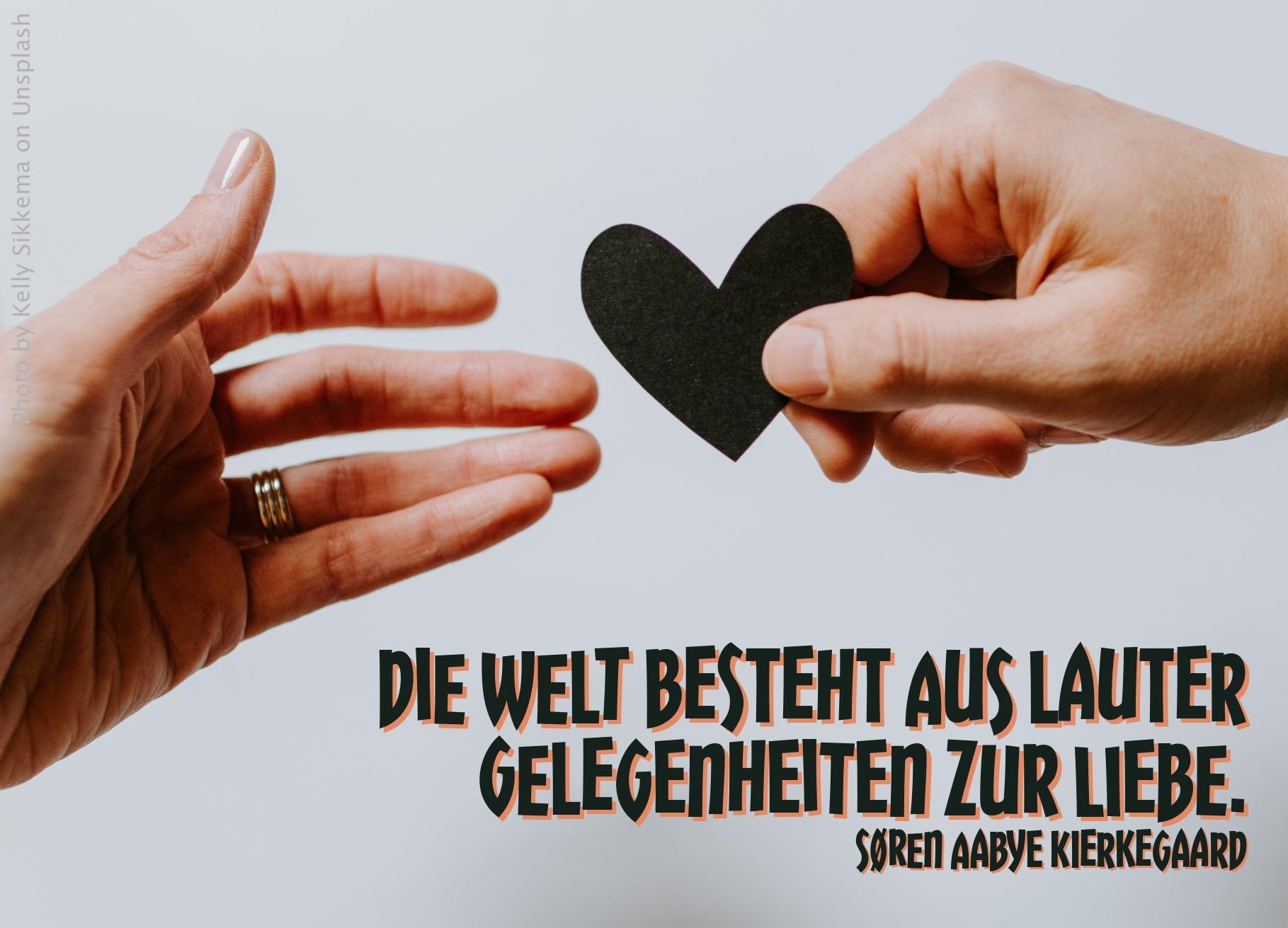 Männerhand überreicht ein schwarzes stilisiertes Herz einer Frauenhand