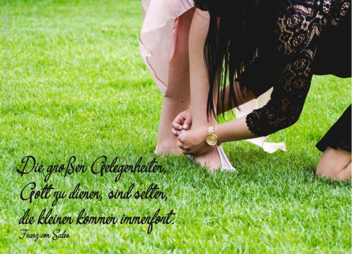Frau bindet anderer Person den Schuh