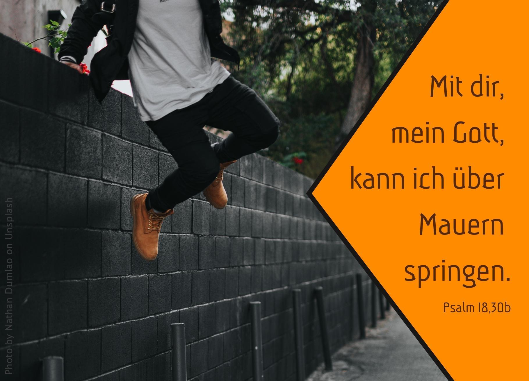 Person springt über Mauer