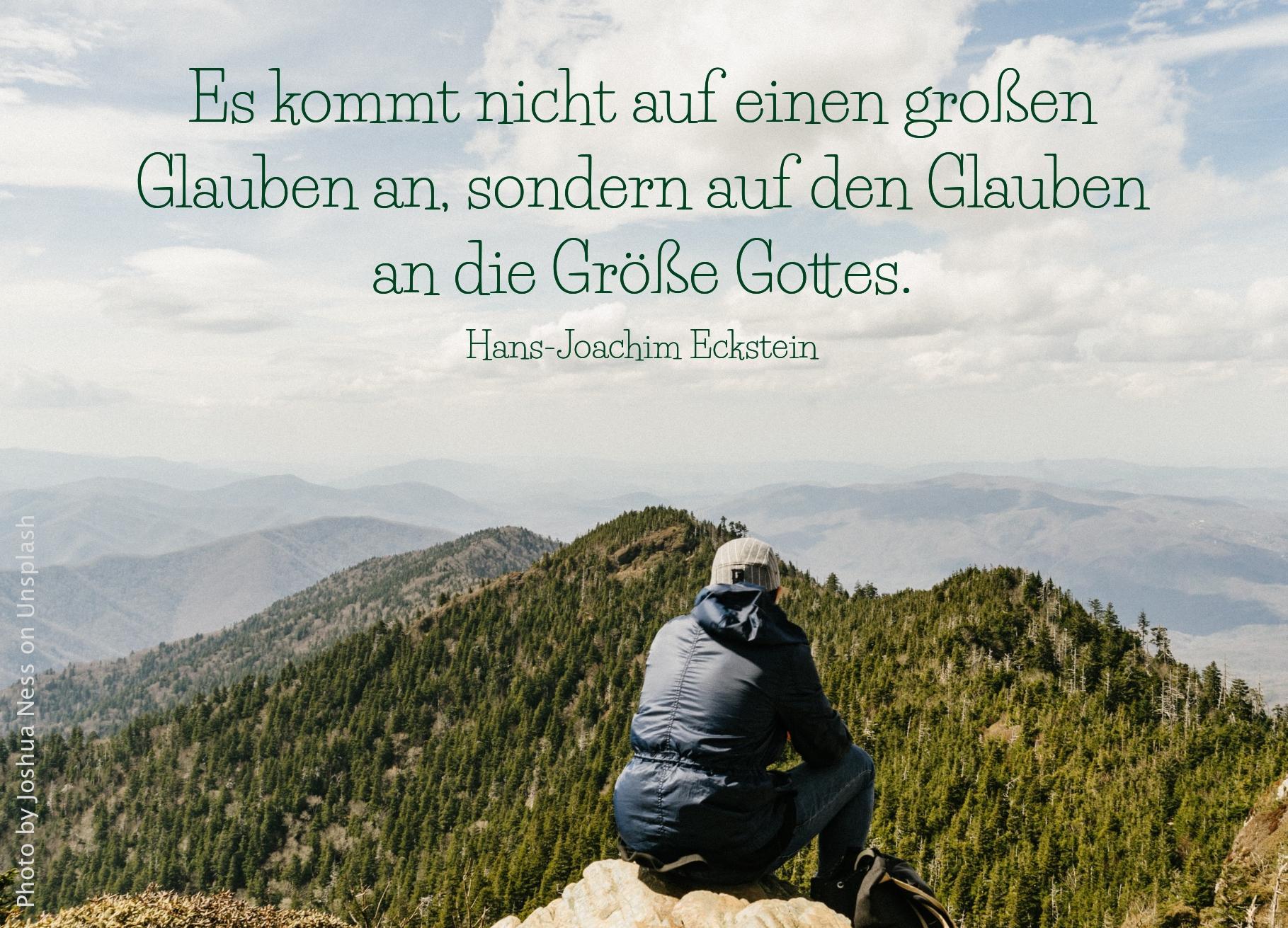 Mann sitzt auf hohem Berggipfel und schaut auf andere Berge