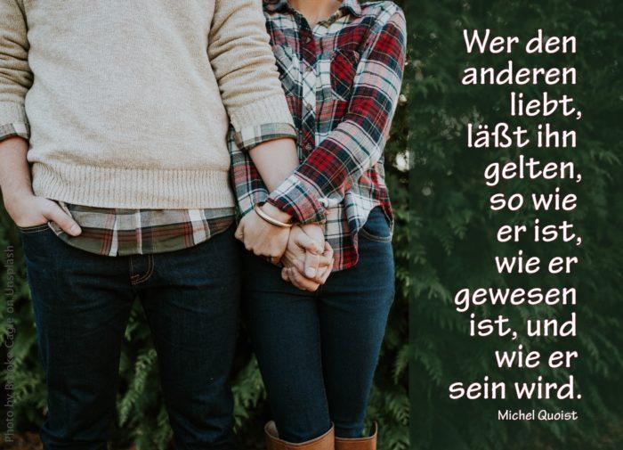 Mann und Frau stehen Hand in Hand vor grünem Busch