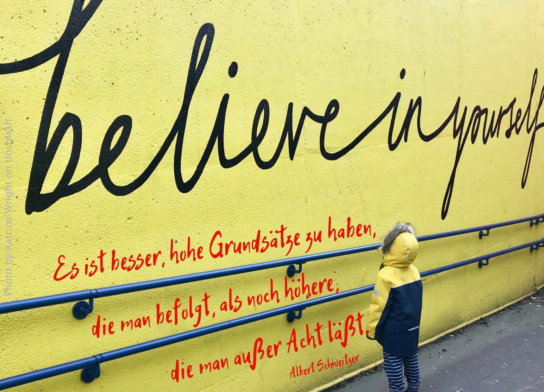 "Kind vor gelber Wand mit den Worten ""belive in yourself"""