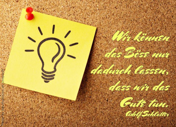 gelber Zettel mit aufgemalter Glühbirne hängt an Kork-Pinnwand