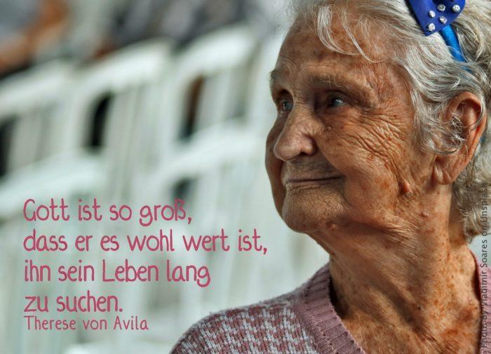 Ältere Frau mit blauer Schleife im Haar guckt zufrieden