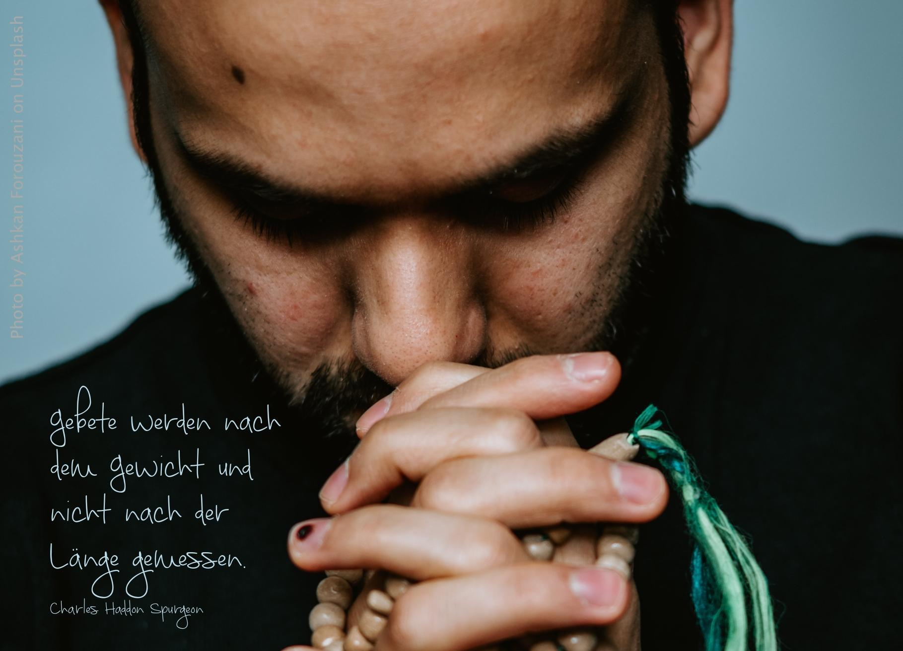 Mann betet mit gefalteten Händen